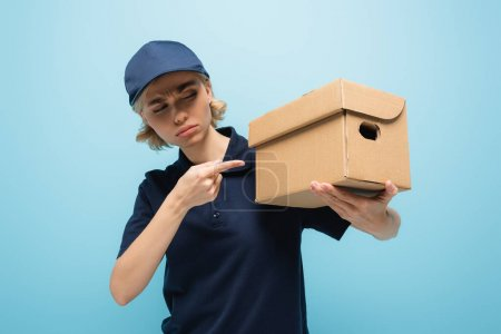 displeased courier pointing at cardboard box isolated on blue