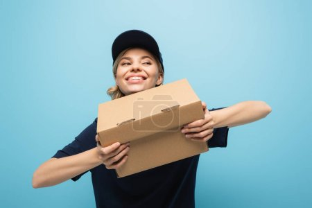 excited courier looking away while holding carton box isolated on blue