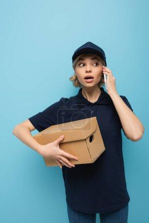 Photo pour Courrier surpris parler sur un téléphone portable tout en tenant boîte de carton isolé sur bleu - image libre de droit