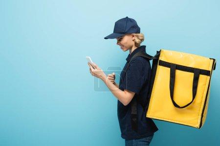 Photo pour Courrier mécontent avec sac à dos thermique regardant smartphone sur bleu - image libre de droit