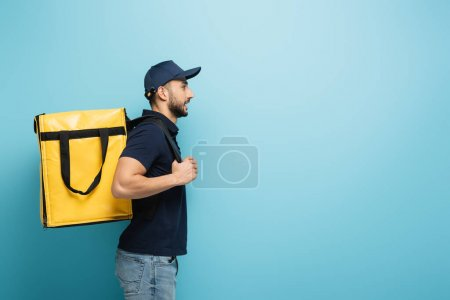 Photo for Side view of muslim delivery man carrying thermo backpack on blue - Royalty Free Image
