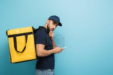 Photo pour Courier arabe coûteux avec sac à dos thermo tenant téléphone moblie sur bleu - image libre de droit