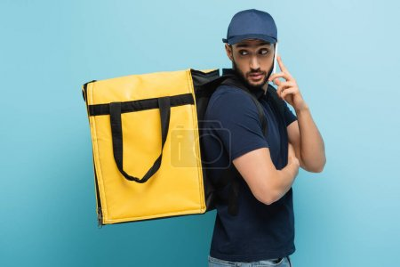 Photo for Arabian courier with thermo backpack talking on mobile phone on blue - Royalty Free Image