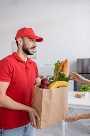 Photo for Woman taking paper bag with fresh food from young muslim delivery man - Royalty Free Image