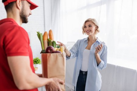 Photo for Blonde woman taking paper bag with food from arabian courier on blurred foreground - Royalty Free Image