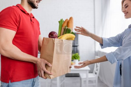 Photo for Delivery man holding fresh food in paper bag near smiling woman - Royalty Free Image