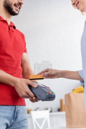 partial view of smiling delivery man holding payment terminal near woman with credit card