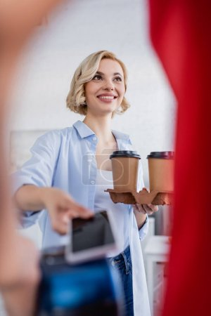 blonde woman holding coffee to go and smartphone near courier on blurred foreground