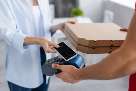cropped view of delivery man holding payment terminal and pizza boxes near woman with mobile phone
