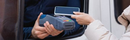 cropped view of delivery man holding payment terminal near woman with mobile phone, banner