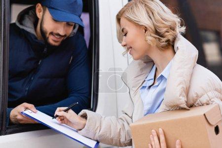 Photo pour Joyeuse femme signer ordre tout en tenant colis près de facteur arabe dans le camion sur fond flou - image libre de droit