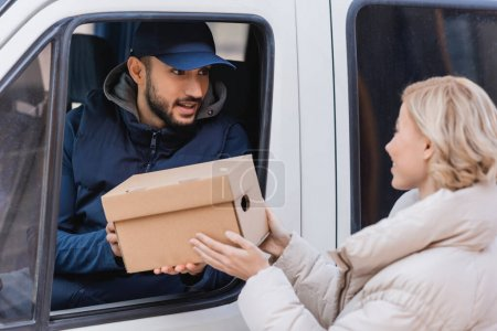 Photo for Muslim postman in truck giving parcel to blonde woman on blurred foreground - Royalty Free Image