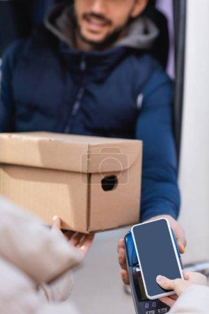 Photo pour Vue recadrée de la femme tenant le colis et payant avec smartphone sur le terminal près du facteur sur fond flou - image libre de droit