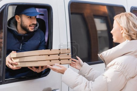 Photo for Arabian delivery man in truck giving pizza boxes to blonde woman - Royalty Free Image