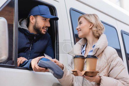 Photo for Arabian delivery man holding payment terminal near blonde woman with credit card and coffee to go - Royalty Free Image