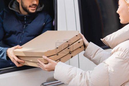 Photo pour Vue partielle du courrier dans la voiture donnant des boîtes de pizza à la femme sur fond flou - image libre de droit