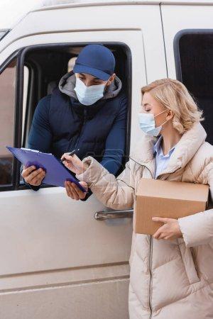 Photo pour Blonde femme signature ordre sur presse-papiers près arabian livraison homme en masque médical - image libre de droit