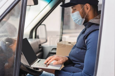 Photo for Arabian delivery man in medical mask typing on laptop while sitting in car - Royalty Free Image