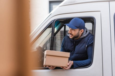 Photo for Muslim delivery man with carton box looking out car window on blurred foreground - Royalty Free Image