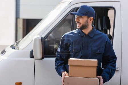 Photo for Smiling arabian courier looking away while holding parcels near car - Royalty Free Image