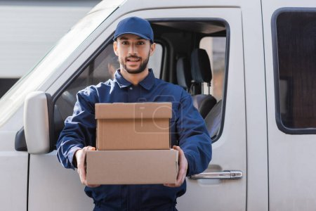 Photo for Young arabian postman holding parcels and looking at camera near car - Royalty Free Image