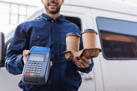 cropped view of delivery man with coffee to go and credit card reader on blurred background