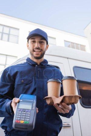 Photo pour Heureux homme de livraison musulman tenant des tasses en papier et terminal de paiement sur le premier plan flou - image libre de droit