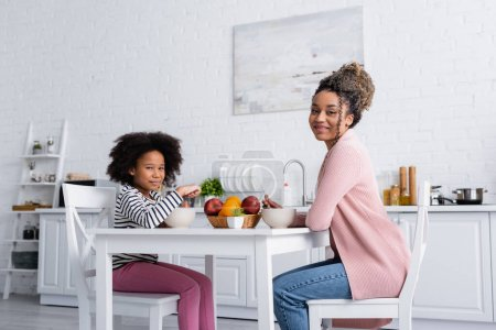 Photo for Happy african american mom and child having breakfast and smiling at camera in kitchen - Royalty Free Image