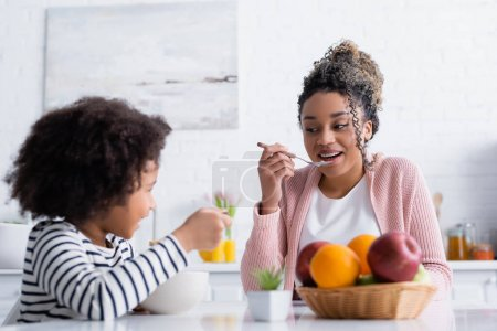 cheerful african american woman looking at daughter while holding spoon with corn flakes, blurred foreground