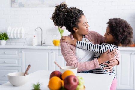 Photo pour Joyeuse mère afro-américaine et sa fille embrassant dans la cuisine près de fruits frais sur le premier plan flou - image libre de droit