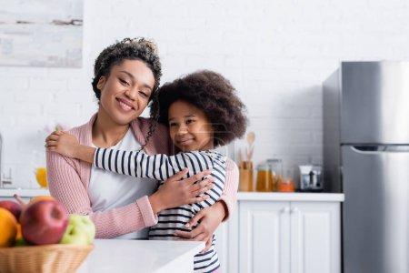 szczęśliwy Afryki amerykański Mama i dziecko uśmiecha się do kamery w pobliżu owoce na zamazanym pierwszy plan