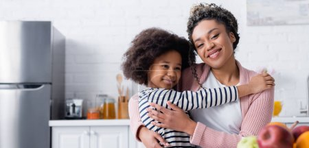 Photo pour Heureuse femme afro-américaine souriant à la caméra tout en embrassant l'enfant dans la cuisine, bannière - image libre de droit
