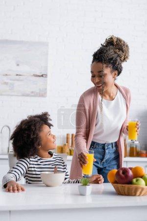 Photo pour Souriant afro-américaine femme regardant fille tout en tenant du jus d'orange - image libre de droit