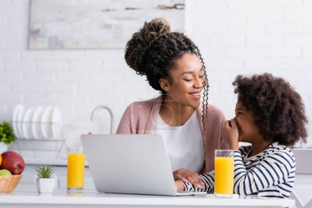 cheerful african american woman looking at laughing daughter while watching movie on laptop in kitchen