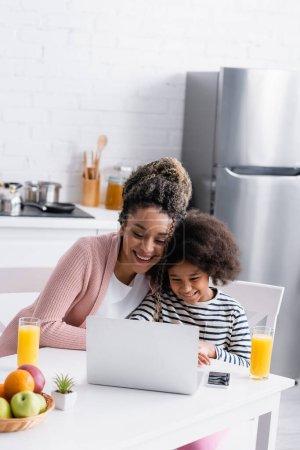 Photo pour Souriant afro-américaine mère et fille regarder un film sur ordinateur portable pendant le petit déjeuner dans la cuisine - image libre de droit