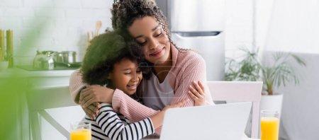 Photo pour Heureux afro-américain mère et fille embrasser tout en regardant le film sur ordinateur portable, flou au premier plan, bannière - image libre de droit