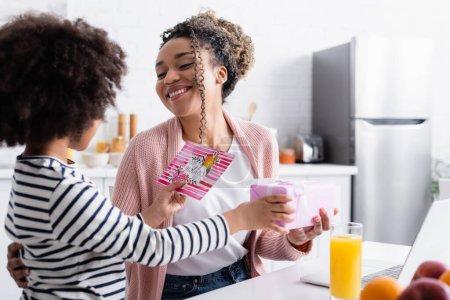 Photo pour Enfant afro-américain présentant cadeau et carte de vœux de la fête des mères à maman heureuse dans la cuisine, premier plan flou - image libre de droit
