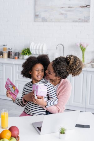 Photo for Happy african american woman embracing daughter holding present and greeting card in kitchen - Royalty Free Image
