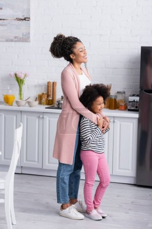cheerful african american woman embracing happy daughter while looking away in kitchen