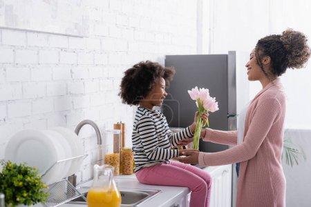 Photo pour Souriant afro-américaine fille assise sur le comptoir de la cuisine et de présenter des tulipes à maman heureuse - image libre de droit