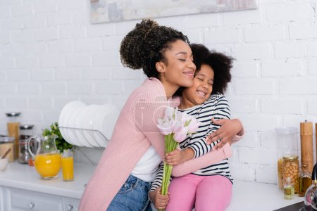 pleased african american woman embracing daughter sitting on kitchen counter with tulips