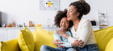 happy african american child and mom embracing with closed eyes on couch at home, banner