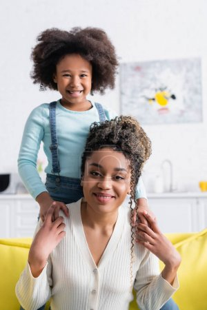 happy african american mother and daughter holding hands and smiling at camera at home