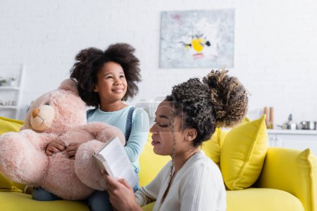 young african american woman reading book to child sitting on couch with teddy bear