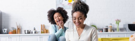 excited african american girl laughing near smiling mother in kitchen, banner