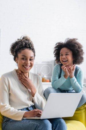 Afrykańska amerykanka uśmiechnięta do kamery przy laptopie i śmiejąca się córka