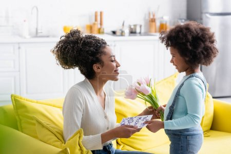 smiling african american child presenting tulips and happy mother day card to happy mom