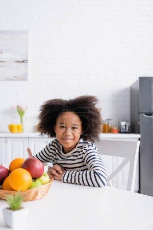 Photo pour Afro-américaine fille souriant à la caméra tout en étant assis dans la cuisine près de fruits frais, flou au premier plan - image libre de droit