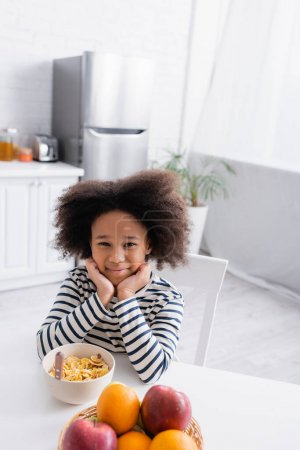 Photo for Joyful african american girl sitting near corn flakes and fresh fruits on kitchen table - Royalty Free Image