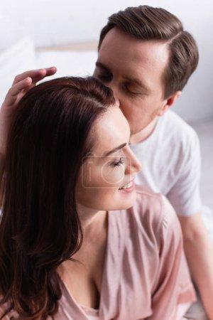 Photo pour Homme embrassant femme souriante avec les yeux fermés dans la chambre - image libre de droit
